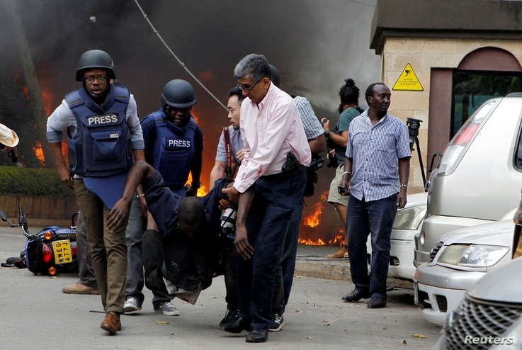 Rescuers and journalists evacuate an injured man from the scene where explosions and gunshots were heard at the Dusit hotel compound, in Nairobi, Kenya, Jan. 15, 2019.