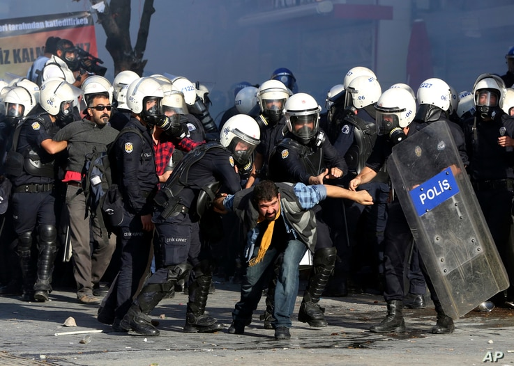 Turkish riot police detain protesters as they use tear gas to disperse people who were protesting against Turkey's policy in Syria as fighting intensified between Syrian Kurds and the militants of Islamic State group in Kobani, Syria, in Ankara, Turk