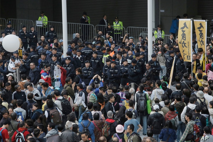 Police officers are surrounded by protesters at the Hong Kong Government Headquarters in Hong Kong, Jan. 1, 2018.