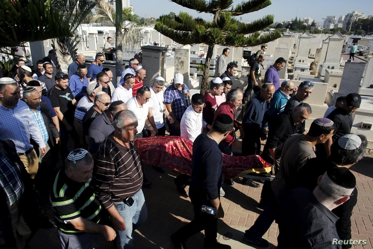 The body of Reuven Aviram, 51, one of two people killed Nov. 19 in a Palestinian stabbing attack in Tel Aviv, is carried by friends and relatives during his funeral in Ramle, Israel, Nov. 20, 2015.