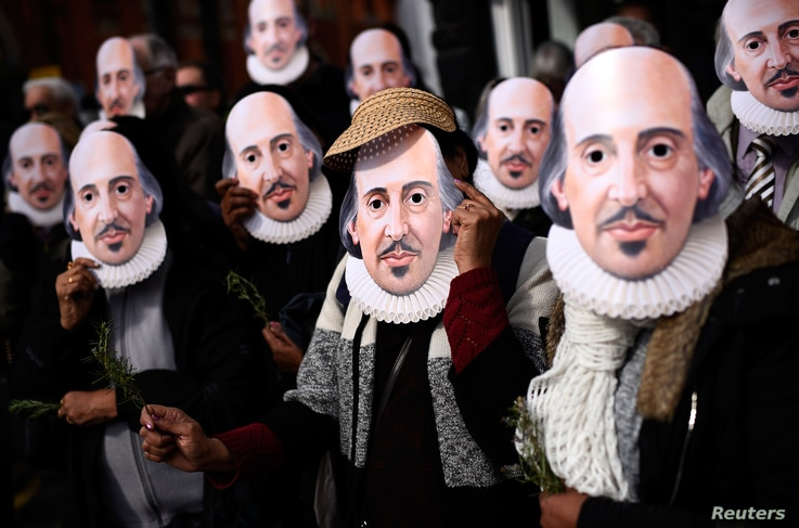 People hold up face masks with William Shakespeare's portrait during celebrations to mark the 400th anniversary of the playwright's death in the city of his birth, Stratford-Upon-Avon, Britain, April 23, 2016.