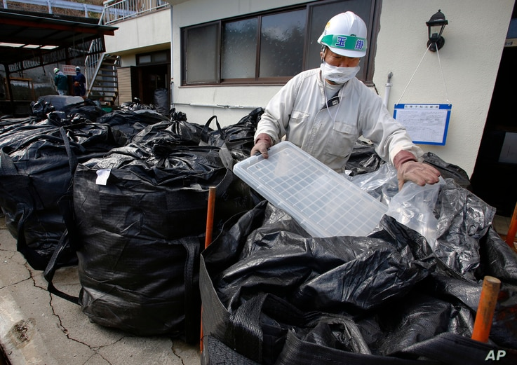 FILE - A worker in a mask collects radioactive trash, placing it in a plastic waste bag at a private house in Minamisoma, Fukushima prefecture, northeastern Japan, Feb. 24, 2016. About 7,000 day laborers are cleaning up this irradiated town.