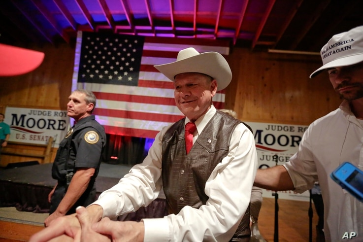Former Alabama chief justice and U.S. Senate candidate Roy Moore shakes hands with supporters after he speaks at a rally, in Fairhope, Alabama, Sept. 25, 2017.