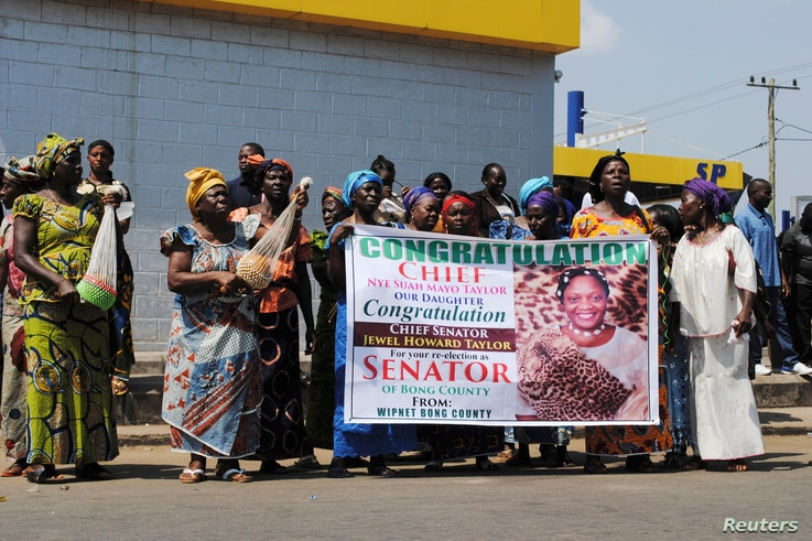 Women hold up a poster congratulating Jewel Howard Taylor, former wife of ex-President Charles Taylor, after she was re-elected senator in Monrovia, Jan. 3, 2015.