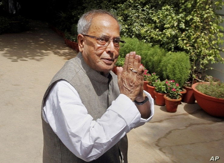 Indian Finance Minister Pranab Mukherjee gestures as he arrives for the Congress Working Committee (CWC) meeting in New Delhi, India, Monday, June 25, 2012.
