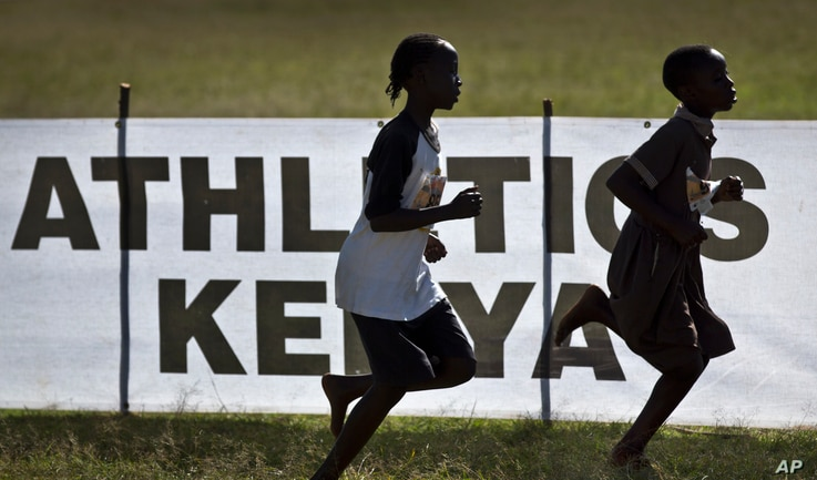 FILE - Junior athletes run past a sign for Athletics Kenya at the Discovery cross country races in Eldoret, western Kenya, Jan. 31, 2016.