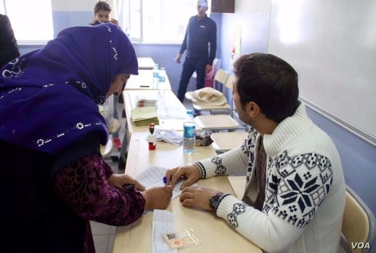 A voter checks in at the polling station in Diyarbakir Sunday morning. VOA journalists in the city report the voting was generally calm, although a few problems occurred.  (Mutlu Civiroglu/VOA),