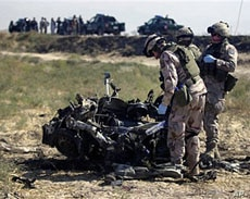 NATO troops from Sweden look at the remains of a suicide bomber's vehicle on the outskirts of Mazar-i-Sharif city in Afghanistan's Balkh province, September 24, 2010