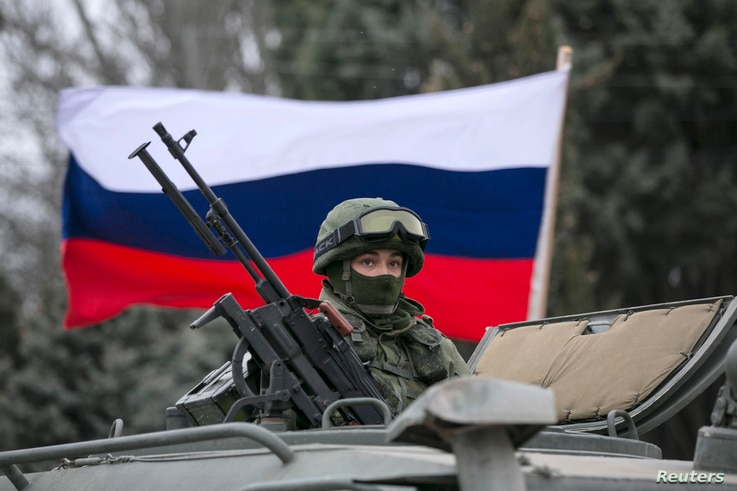 A pro-Russian man (not seen) holds a Russian flag behind an armed servicemen on top of a Russian army vehicle outside a Ukrainian border guard post in the Crimean town of Balaclava, March 1, 2014.