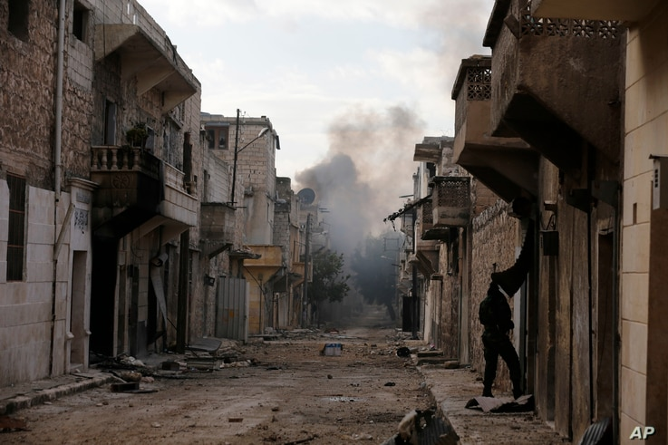 Smoke rises in the east Aleppo neighborhood of Tariq al-Bab after insurgents militants launch a mortar shell on government soldiers in Syria, Dec. 3, 2016.