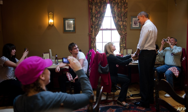 Barack Obama shakes hands with customers at the Common Man restaurant in Merrimack, New Hampshire, October 27, 2012, during an unscheduled campaign stop.