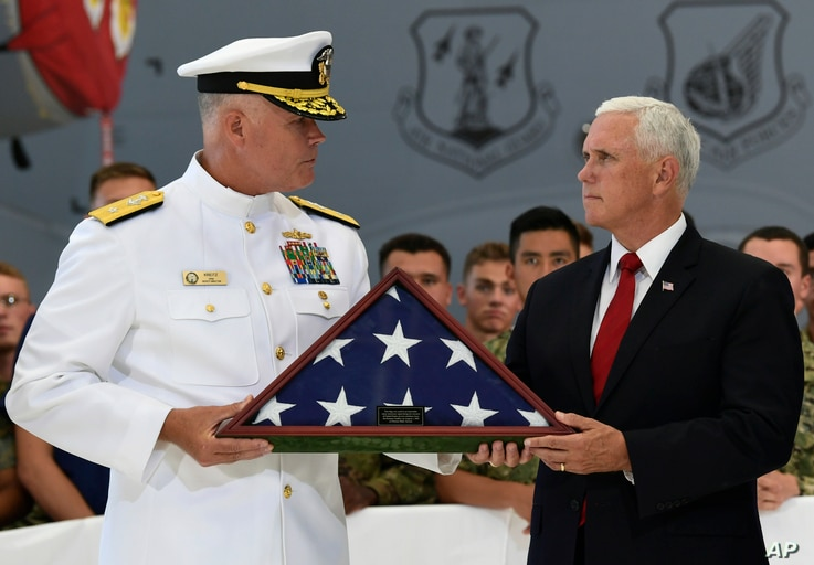Vice President Mike Pence (R) receives a flag from Navy Rear Adm. Jon Kreitz, deputy director of the POW/MIA Accounting Agency during a visit to Joint Base Pearl Harbor-Hickam in Hawaii, Aug. 1, 2018.