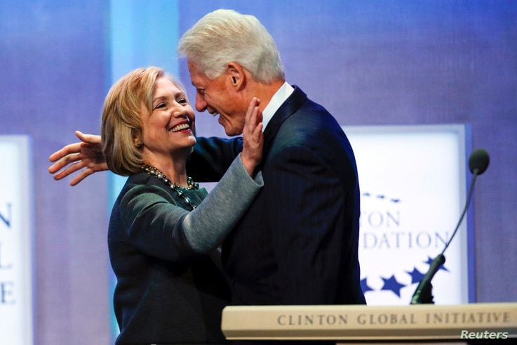 "Former U.S. President Bill Clinton and former U.S. Secretary of State Hillary Clinton embrace during the opening plenary session labeled ""Reimagining Impact"" at the Clinton Global Initiative 2014 (CGI) in New York, September 22, 2014."