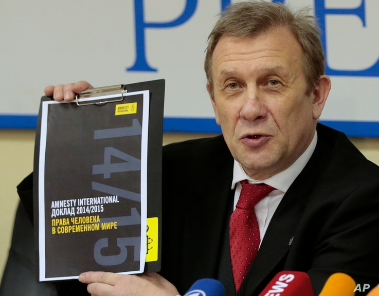Sergei Nikitin, director of Amnesty International representative office in Russia, shows a copy of company's report on human rights during a news conference in Moscow, Russia, on Tuesday, Feb. 24, 2015.