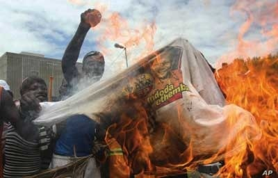Supporters of the fledgling National Freedom Party, the NFP, burn T-shirts bearing the image of Inkatha Freedom Party, IFP, leader Mangosuthu Buthelezi in Durban, South Africa, recently
