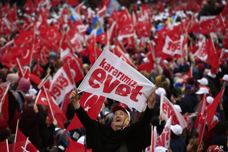 A supporter of Turkey's President Recep Tayyip Erdogan, waiting for his speech, waves a banner that reads in Turkish: 'Our decision is Yes', referring to the upcoming referendum, during a rally in the Black Sea city of Rize, Turkey, April 3, 2017.