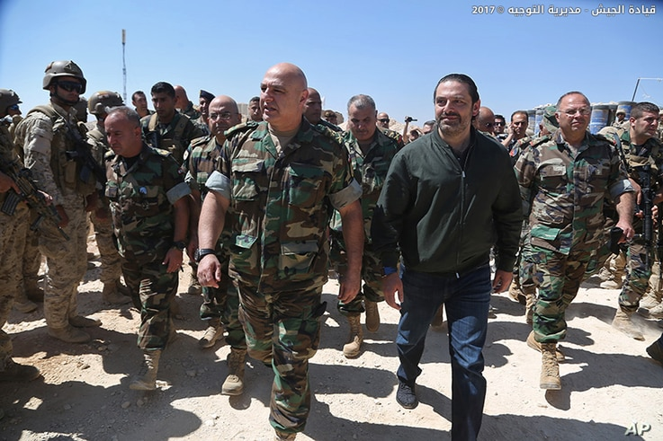 n this photo released by the Lebanese Army official website, Lebanese Prime Minister Saad Hariri, center right, walks with Lebanese Army Commander Gen. Joseph Aoun, center left,  during a visit to the command center for the ongoing military operation...