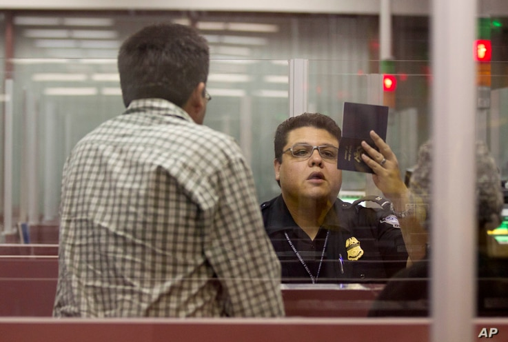 FILE - A Customs and Border Protection officer checks the passport of a non-resident visitor to the United States inside immigration control at McCarran International Airport, Tuesday, Dec. 13, 2011, in Las Vegas.