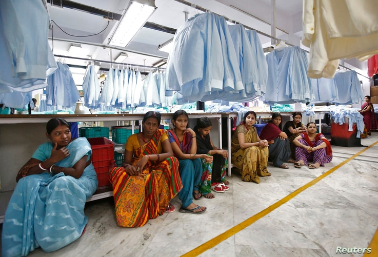 FILE - Employees sit during their lunch time inside a textile mill in India, April 16, 2014.