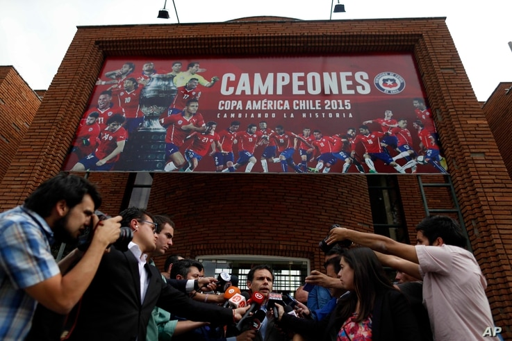 Government Attorney Carlos Gajardo, center, speaks to the press, in front of Chile's National Association of Professional Soccer, ANFP, after police investigators entered the building to look for documents and computers from the office of former pres...