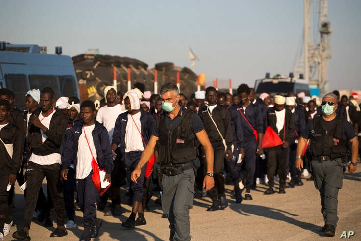 Italian border police officers escort sub Saharan men on their way to a relocation center, after arriving aboard the Golfo Azzurro rescue vessel at the port of Augusta, in Sicily, Italy, June 23, 2017.