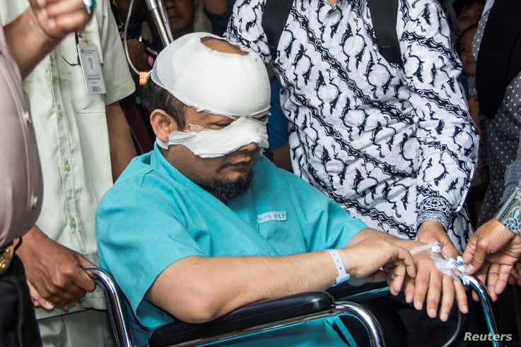 FILE - Novel Baswedan, an investigator at the country's Corruption Eradication Commission (KPK), sits in a wheelchair on his way to an eye hospital for special treatment after an unidentified attacker threw acid at him, in Jakarta, Indonesia, April 1...