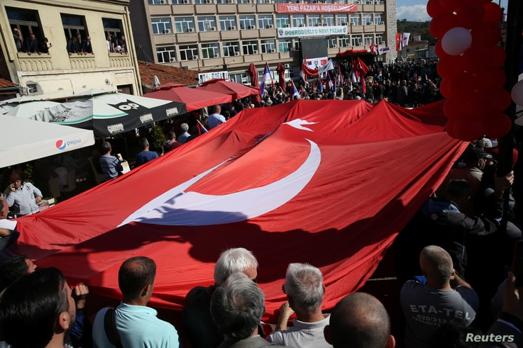 FILE - People carry the Turkish flag as Turkish President Recep Tayyip Erdogan and his Serbian counterpart, Aleksandar Vucic, visit Novi Pazar, Serbia, Oct. 11, 2017.