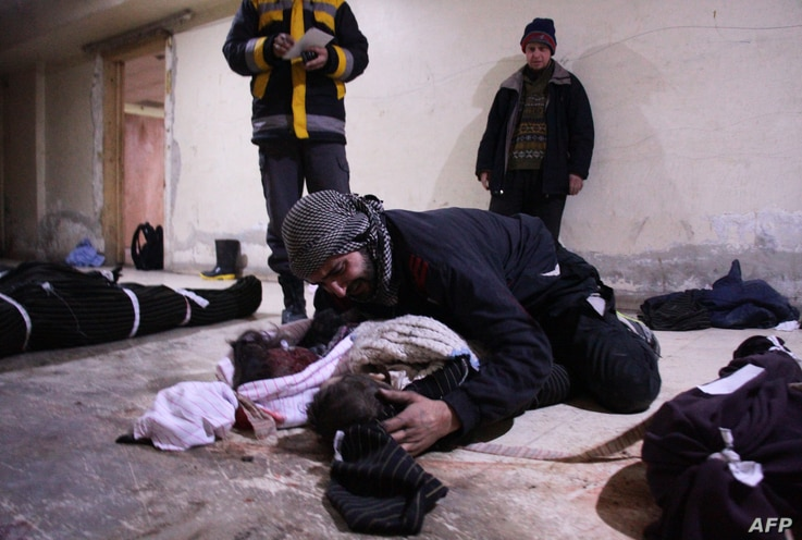 Graphic content / A man weeps over his child at a make-shift morgue in Douma who was killed in air strikes on the Syrian village of Mesraba in the besieged Eastern Ghouta region on the outskirts of the capital Damascus, Feb. 19, 2018.