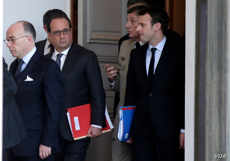 From left, French Interior Minister Bernard Cazeneuve and President Francois Hollande and other officials walk out of the Elysee Palace after a Defense council meeting following attacks Friday in Paris, France, Nov. 14, 2015.