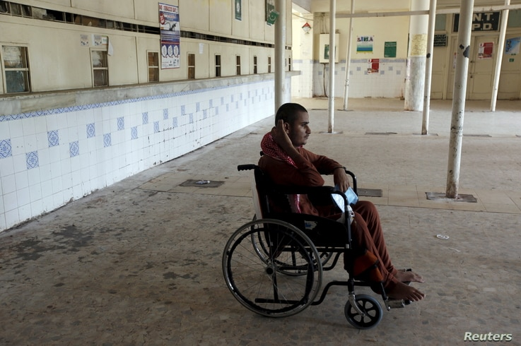 FILE - A patient in a wheelchair waits at a medical center in Karachi, Pakistan, Sept. 17, 2015.