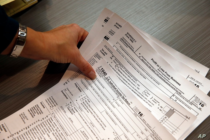 Tax professional and tax preparation firm owner Alicia Utley reaches for hard copies of tax forms at the start of the tax season rush in her offices in Boulder, Colo., Jan. 14, 2017.