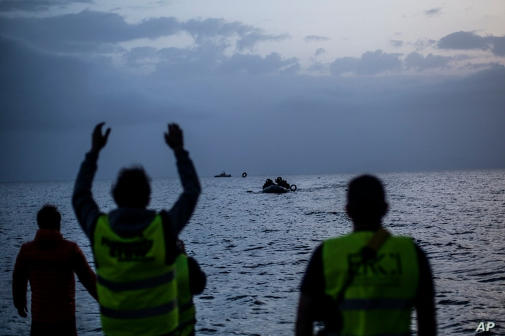 Volunteers guide an overcrowded dingy with refugees and migrants as it is approaches the beach after crossing a part of the Aegean sea from Turkey to the Greek island of Lesbos, Feb. 19, 2016.