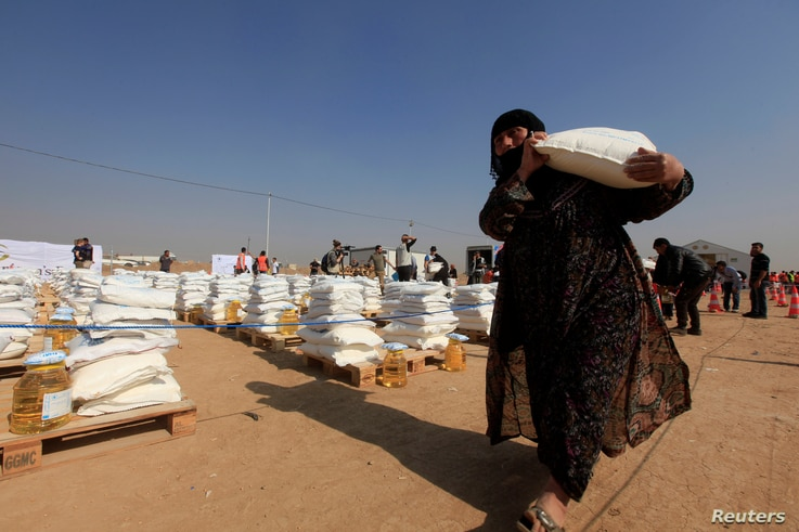 A displaced woman, who fled from Mosul due to Islamic State violence, carries food in Khazer refugee camp, east of Mosul, Iraq November 7, 2016.  Humanitarian aid officials are preparing to care for up to 700,000 refugees due to the fighting in and a