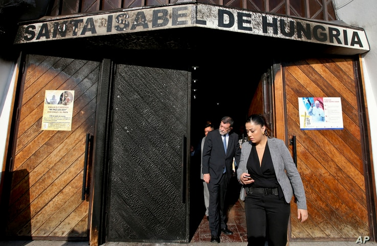 Deputy Interior Secretary Aleuy Mahmud, center, exits the Santa Isabel de Hungria Catholic Church, past a door damaged in an overnight fire-bomb attack, in Santiago, Chile, Jan. 12, 2018. On the eve of a papal visit, vandals fire-bombed three churche...