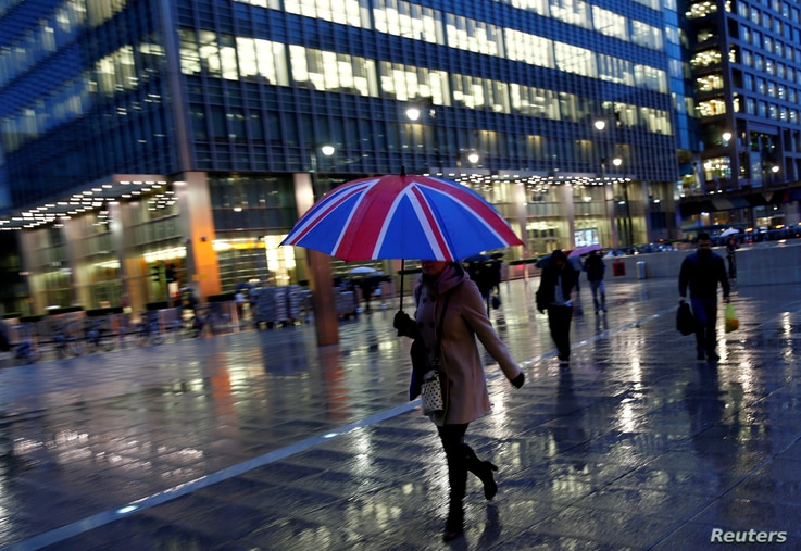 FILE: Workers walk in the rain at the Canary Wharf business district in London, Britain, November 11, 2013.