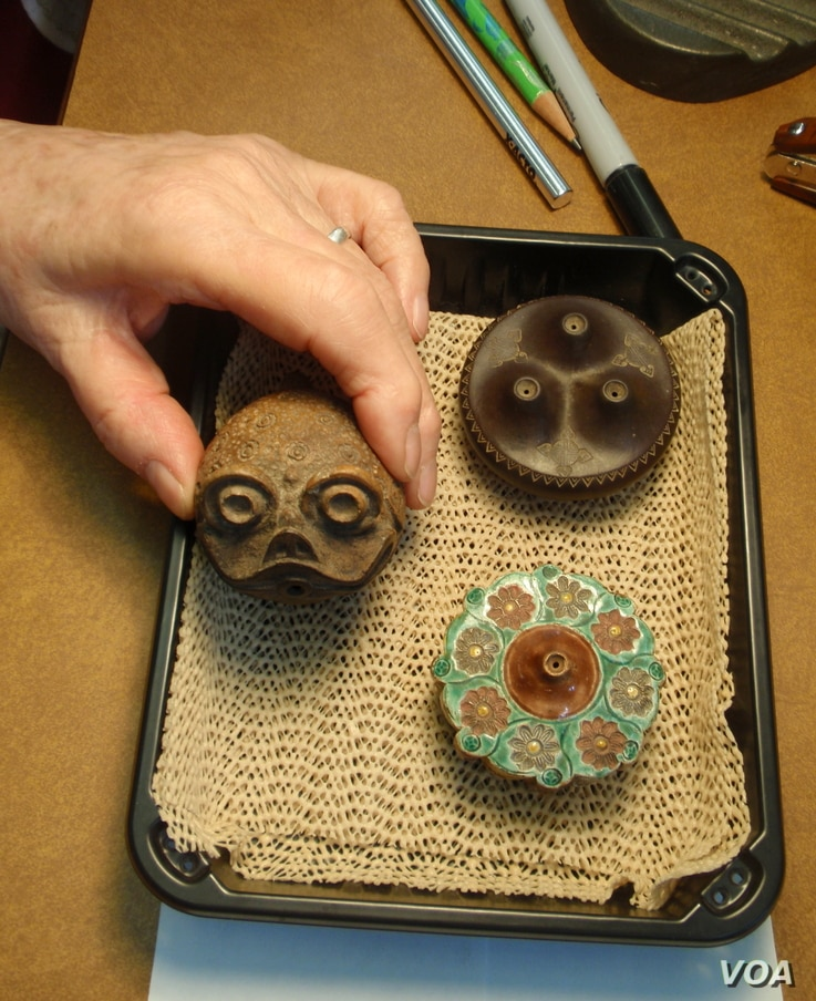 Ceramic opium pipe bowls; the center one has a toad design.(VOA/T. Banse)
