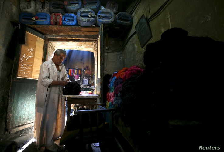 Salama Mahmoud Salama, 75, the owner of a dye workshop looks at yarns at the workshop in old Cairo, Egypt, March 17, 2016.