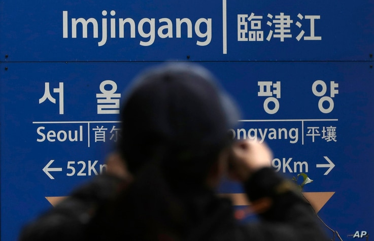 A woman takes a photo in front of a signboard showing the distance to North Korea's capital Pyongyang and to South Korea's capital Seoul from Imjingang Station in Paju, South Korea, Nov. 24, 2018. South Korea said Saturday that the United Nations Sec...