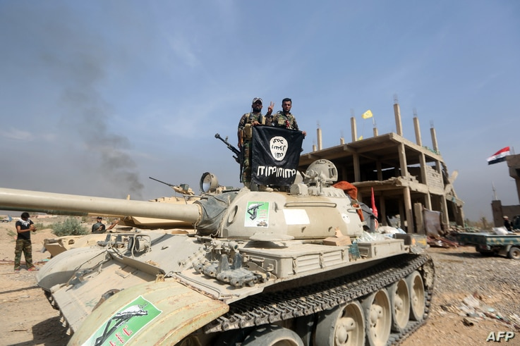 Iraqi Shiite fighters from the Popular Mobilisation units, fighting alongside Iraqi government forces, display, upside down, the flag of the Islamic State (IS) group during a military operation aimed at the centre of Baiji, Iraq, Oct. 19, 2015.