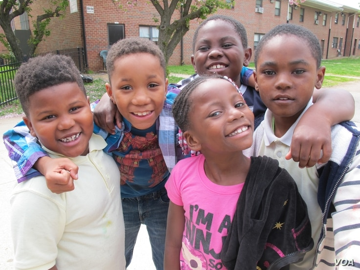 Some youngsters clamor to be photographed near McCulloh Homes, a housing project in Baltimore, Maryland.
