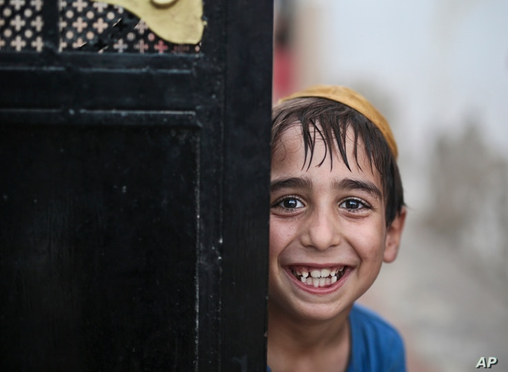 A student covering his head with a Kippah grins for the camera as he leaves the main Talmudic school at Hara Kbira, the main Jewish neighborhood on the Island of Djerba, southern Tunisia, Oct. 29, 2015..