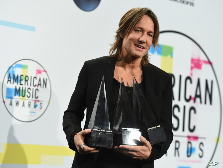 """Keith Urban poses in the press room with the awards for favorite male artist country, favorite song country for """"Blue Ain't Your Color"""" and favorite album country for """"Ripcord"""" at the American Music Awards at the Microsoft Theater on Sunday, Nov. 19,..."""