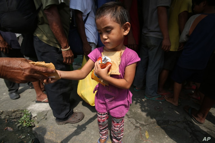 A poor Filipino girl holds bread and drinks she received during a feeding program by Dominican nuns in Manila, Philippines on Wednesday, Sept. 17, 2014.