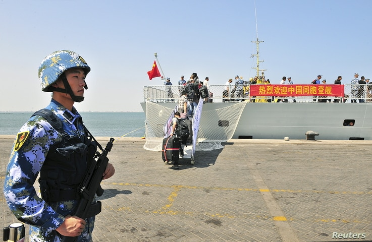 """FILE - A navy soldier (L) of People's Liberation Army (PLA) stands guard as Chinese citizens board the naval ship """"Linyi"""" at a port in Aden."""