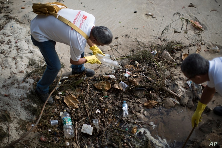Health agents remove plastic bottles during an operation to eradicate the Aedes aegypti mosquito in Niteroi, Brazil, March 8, 2016.