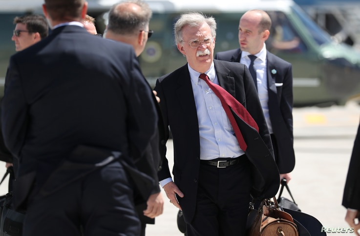 U.S. President Donald Trump's National Security Adviser John Bolton carries a bag as he arrives to board Air Force One to depart for travel to Singapore from Quebec, Canada, June 9, 2018.