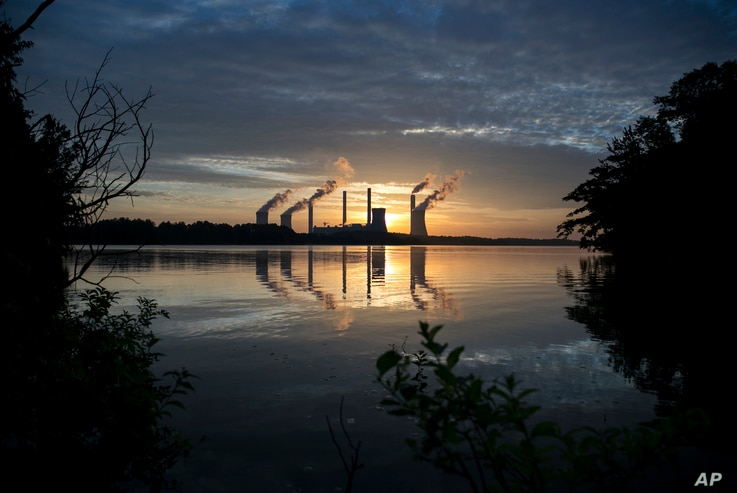 FILE - The coal-fired Plant Scherer, one of the nation's top carbon dioxide emitters, stands in the distance in Juliette, Ga., June, 3, 2017. U.S. President Donald Trump on June 1, 2017, pulled the U.S. from the Paris climate agreement, striking a ma...
