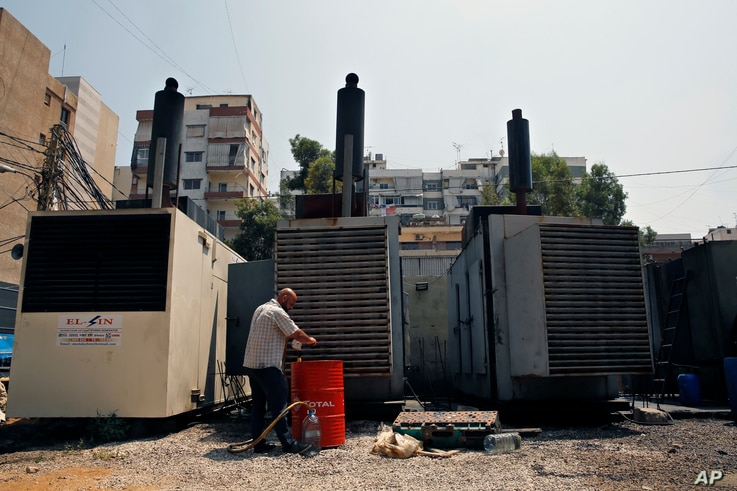 This July 16, 2018, photo shows Mamdouh al-Amari oiling privately-owned diesel generators that provide power to homes and businesses, in the southern suburbs of Beirut, Lebanon.