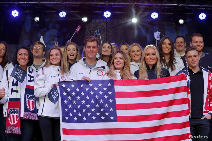 Olympians hold a flag at an event in Times Square to celebrate 100 days from the start of the Pyeongchang 2018 Olympic Games in South Korea, in New York, Nov. 1, 2017.