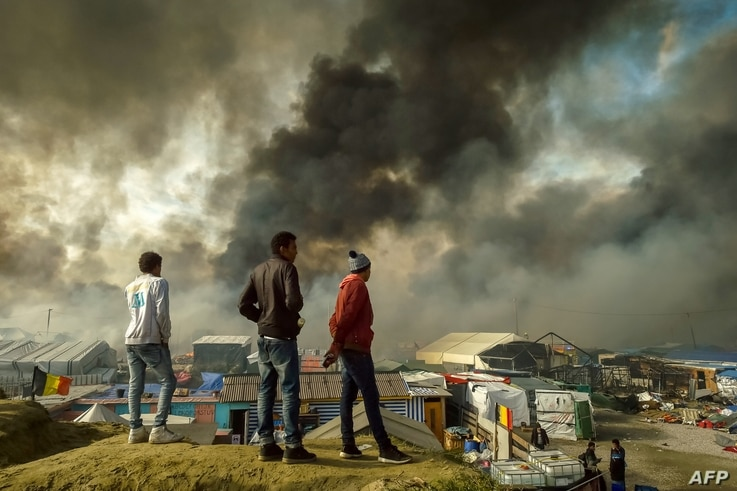 "Migrants stand on a hill overlooking the ""Jungle"" migrant camp in Calais, northern France, as smoke rises, Oct. 26, 2016, during a massive operation to clear the squalid settlement where 6,000-8,000 people have been living in dire conditions."